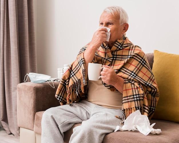 Średnio strzał chory mężczyzna trzyma kubek