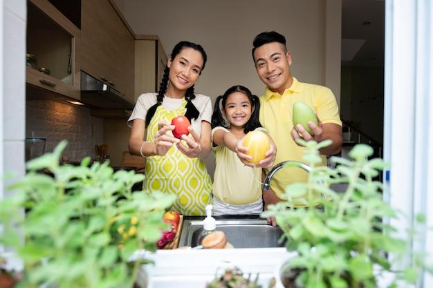 Średnio strzał członków rodziny trzymających owoce