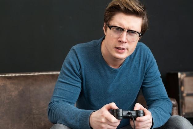 Średnio strzał człowiek w okularach, grając z kontrolerem