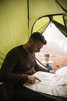 Średnio strzał człowieka z mapą w namiocie