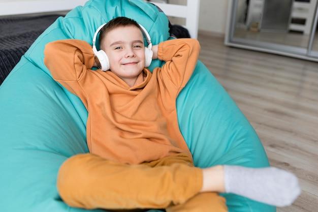Średnio strzał dzieciak siedzący na krześle worek fasoli