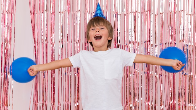 Średnio strzał dzieciak trzymający niebieskie balony