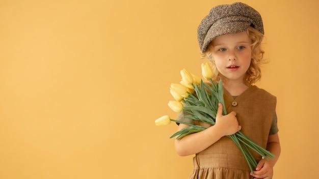Średnio strzał dziecko trzymające kwiaty