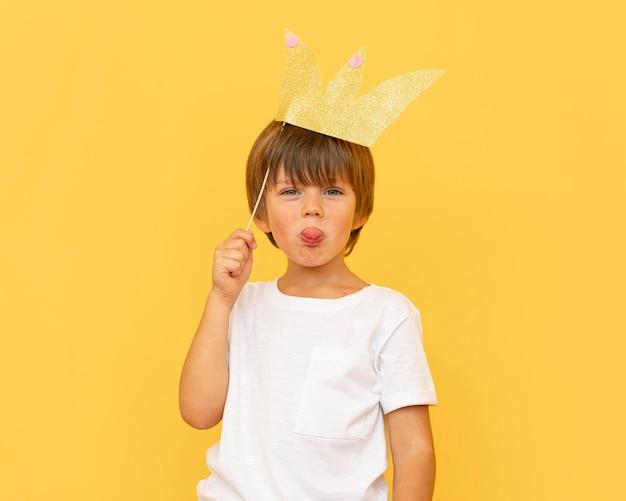 Średnio strzał dziecko trzymające papierową koronę