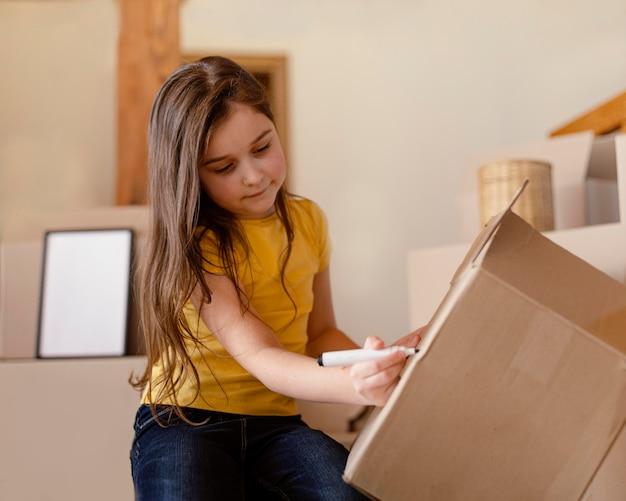 Średnio strzał dziewczyna pisze na pudełku