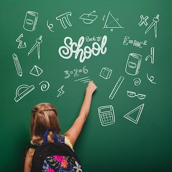 Średnio strzał dziewczyna pisze na zielonej tablicy
