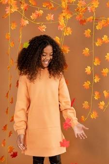 Średnio strzał dziewczyna pozuje z liśćmi