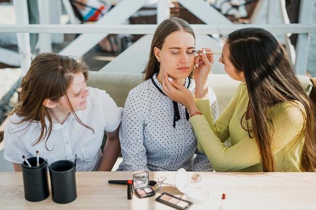 Średnio strzał dziewczyna robi makijaż od przyjaciela