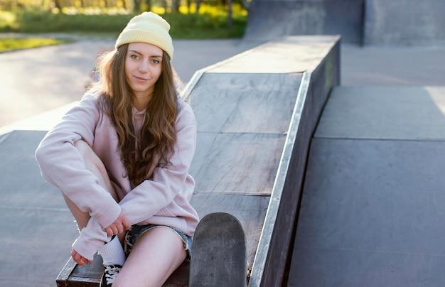 Średnio strzał dziewczyna siedzi z skate