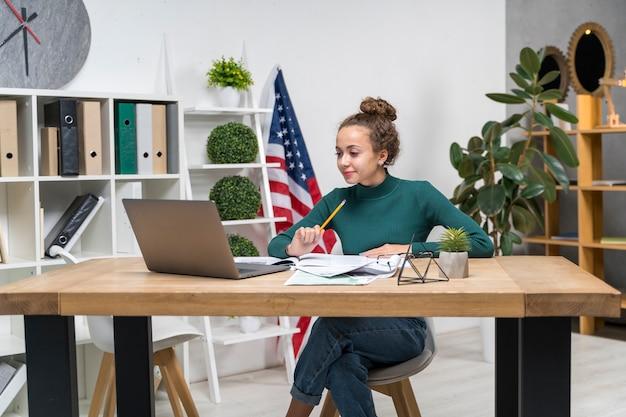Średnio strzał dziewczyna studiuje przy biurku w pomieszczeniu