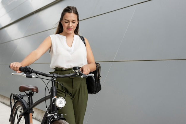 Średnio strzał dziewczyna trzyma kierownicę roweru