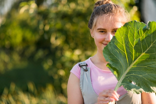 Średnio strzał dziewczyna trzyma liść sałaty