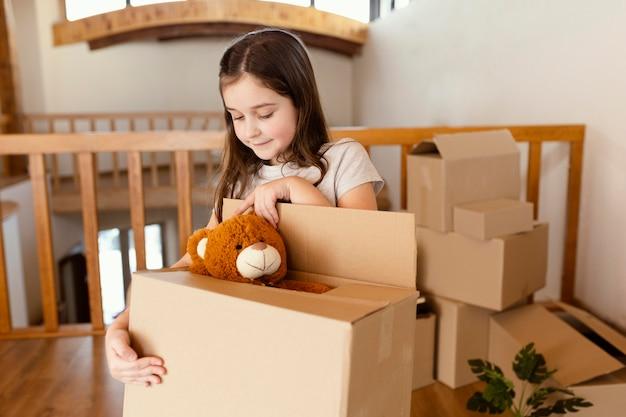 Średnio strzał dziewczyna trzyma pudełko z zabawkami