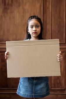 Średnio strzał dziewczyna trzyma pusty plakat