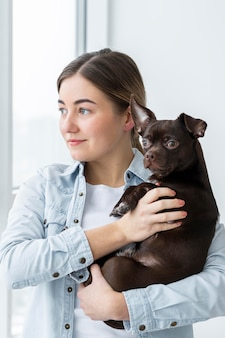 Średnio strzał dziewczyna trzyma słodkiego psa
