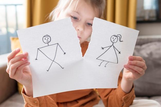 Średnio strzał dziewczyna trzyma uszkodzony rysunek