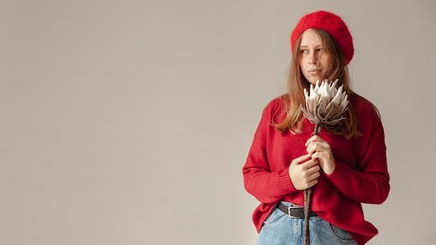 Średnio strzał dziewczyna z czerwonym kapeluszu i pozowanie kwiat
