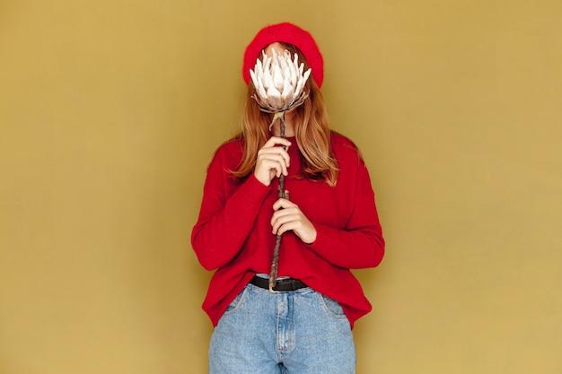 Średnio strzał dziewczyna z kwiatem i żółtym tle