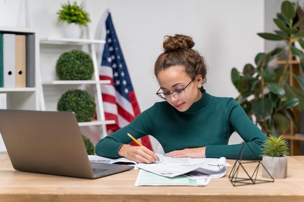 Średnio strzał dziewczyna z laptopa pisania przy biurku
