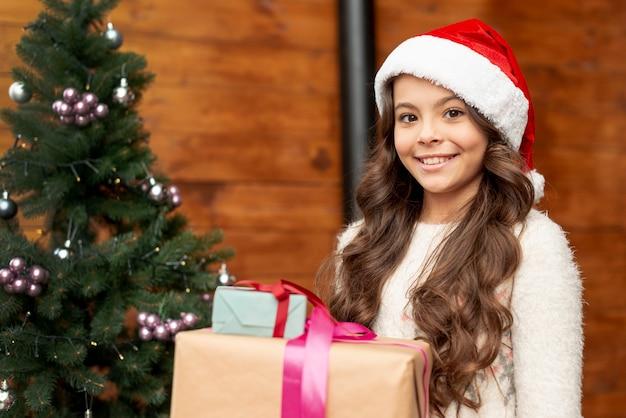Średnio strzał dziewczyna z prezentami, patrząc na kamery