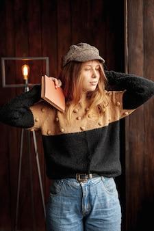 Średnio strzał dziewczyna ze stawianiem książki i kapelusz
