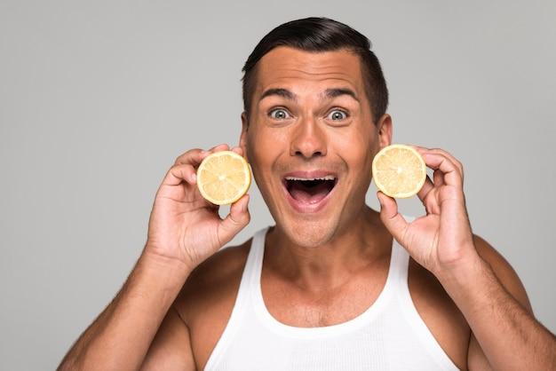Średnio strzał ekscytujący mężczyzna trzyma cytryny