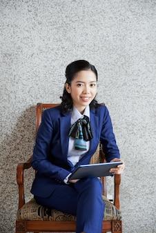Średnio strzał etnicznej kobiety biznesu siedzi z komputera typu tablet obok szarej ściany