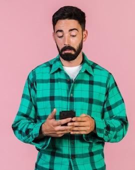 Średnio strzał facet patrząc na telefon