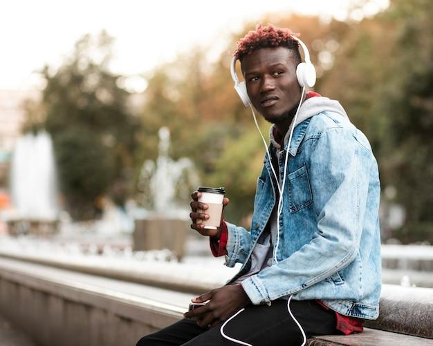 Średnio strzał facet ze słuchawkami i filiżanką kawy