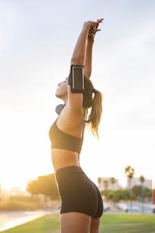 Średnio strzał fit kobieta rozciągająca się na zewnątrz