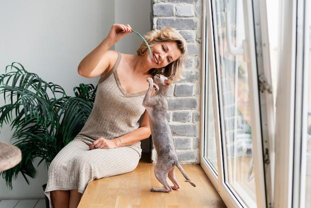 Średnio strzał kobieta bawiąca się z kotem