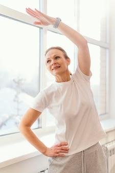 Średnio strzał kobieta ćwiczeń w pomieszczeniu