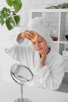 Średnio strzał kobieta czyszcząca twarz