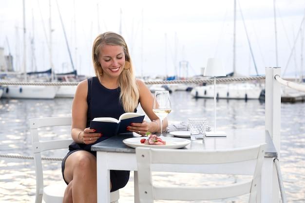 Średnio strzał kobieta czytająca przy stole