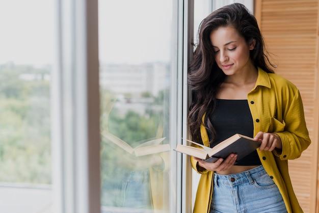 Średnio strzał kobieta czytająca w pobliżu okna
