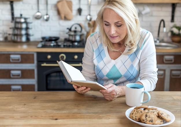 Średnio strzał kobieta czytanie w kuchni