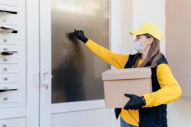 Średnio strzał kobieta dostawy trzymając pudełko