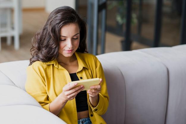 Średnio strzał kobieta gra na telefon