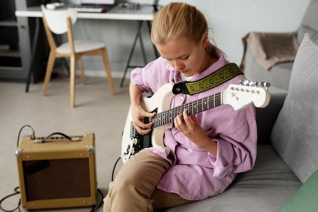 Średnio strzał kobieta grająca na gitarze