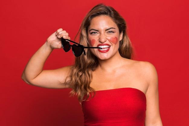 Średnio strzał kobieta gryzie okulary przeciwsłoneczne