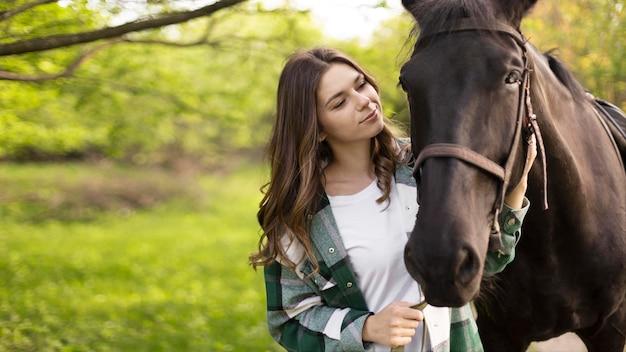 Średnio strzał kobieta i koń na zewnątrz