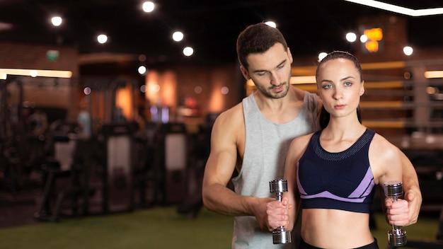 Średnio strzał kobieta i trener na siłowni