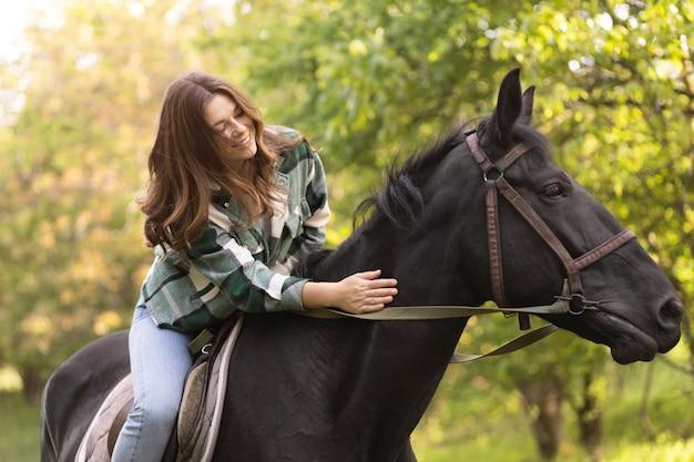 Średnio strzał kobieta jedzie na koniu
