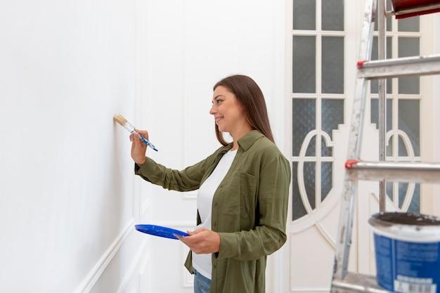 Średnio strzał kobieta malująca ścianę