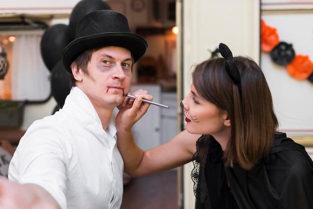 Średnio strzał kobieta malująca twarz mężczyzny