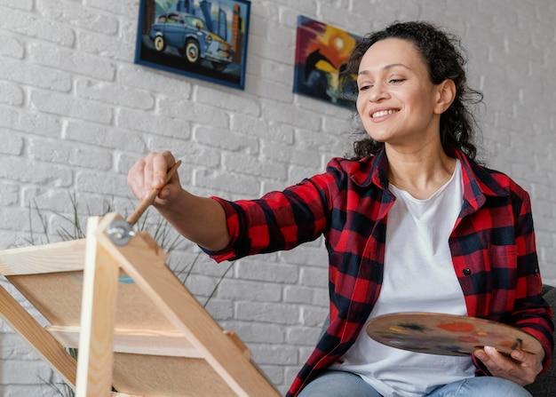 Średnio strzał kobieta malująca w domu
