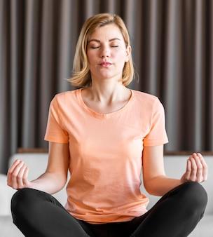 Średnio strzał kobieta medytuje w pomieszczeniu