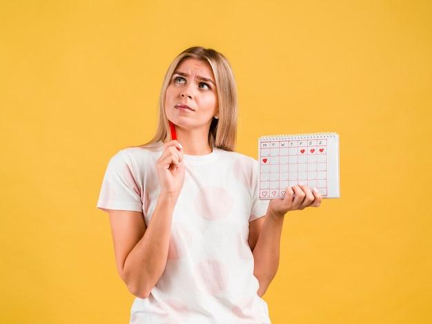Średnio strzał kobieta myśli i trzyma kalendarz okresu