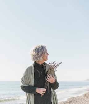Średnio strzał kobieta na plaży z kwiatami
