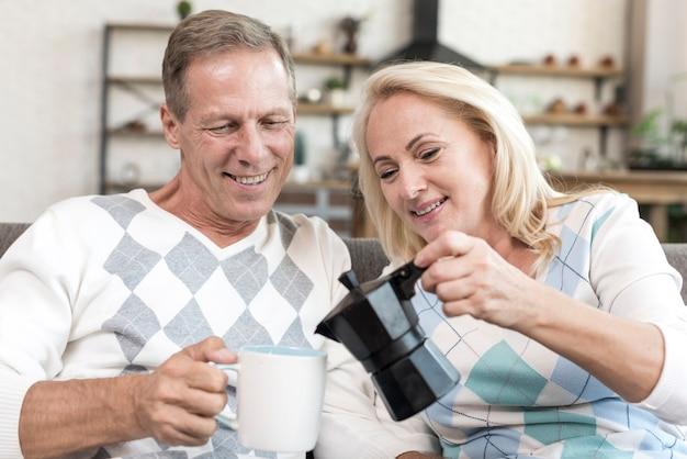 Średnio strzał kobieta nalewanie kawy do mężczyzny